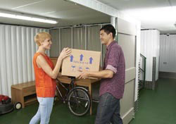 man and lady from peterborough moving household items into self storage unit at morespace near peterborough in cambridgeshire