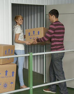 couple from st neots moving boxes into self storage unit at morespace near st neots in cambridgshire