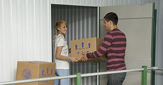 couple from cambourne storing moving boxes into self storage facility at morespace near cambourne in cambridgeshire